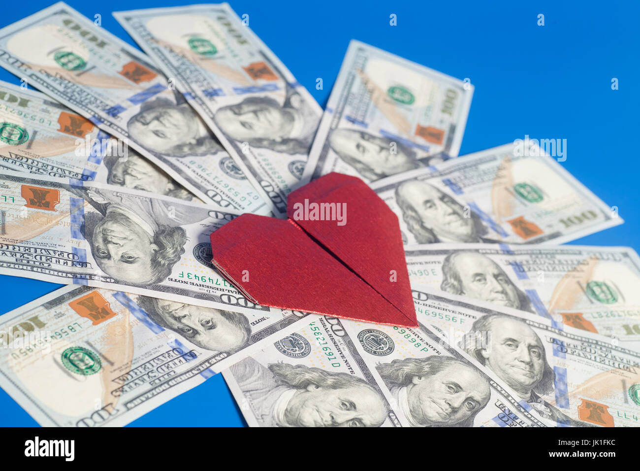 Red paper heart origami and dollar bills on blue background stock red paper heart origami and dollar bills on blue background jeuxipadfo Images