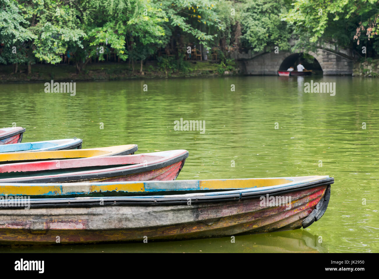 Old multicolored boats on a lake with trees and stone bridge in the ...