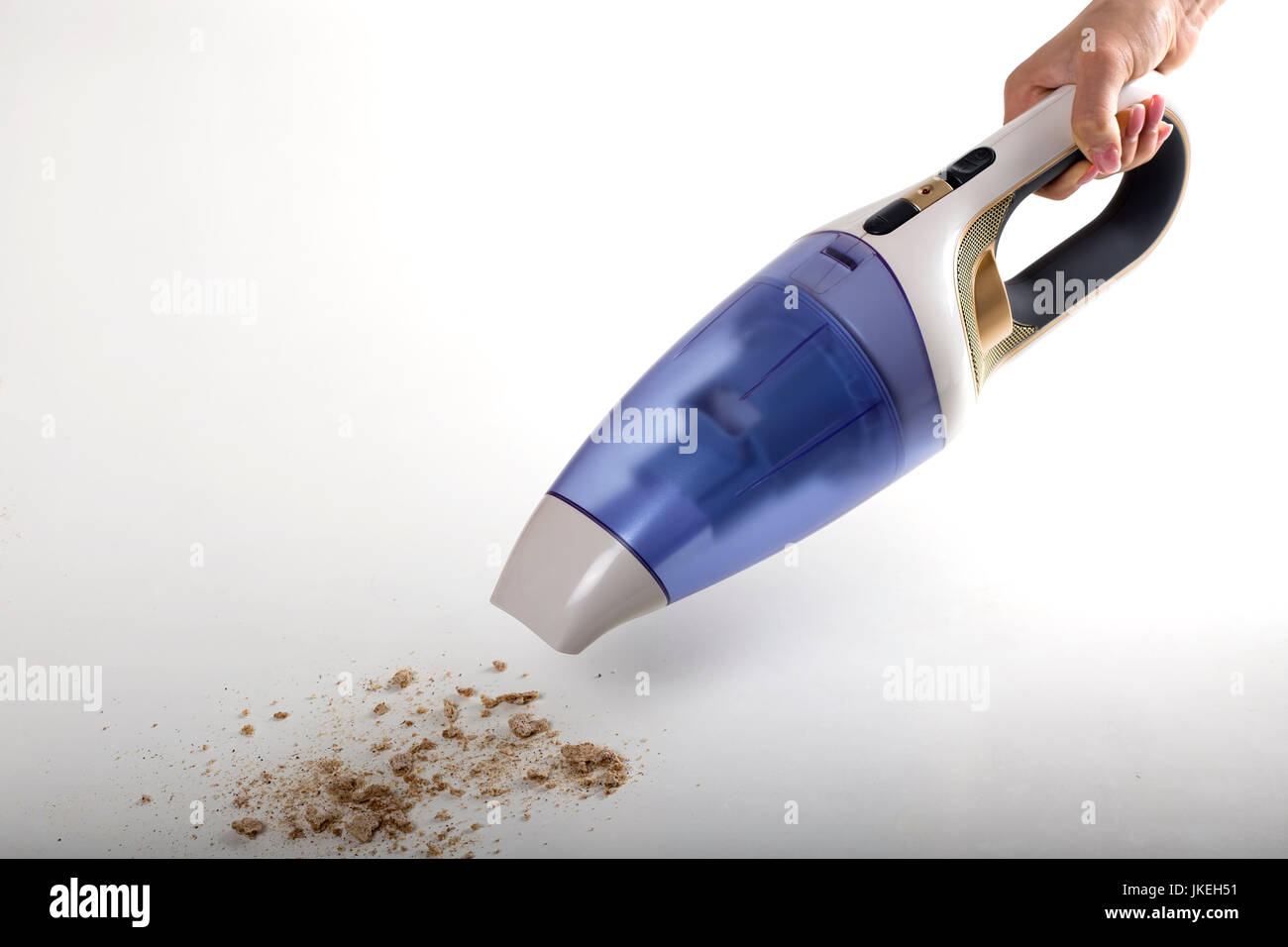 Female Hand Cleaning Bread Crumbs With A Portable Vacuum Cleaner