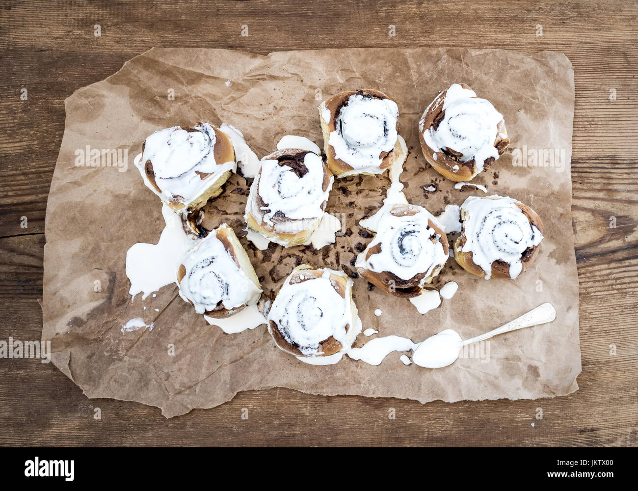 Cinnamon rolls with cream cheese icing on piece of oily craft cinnamon rolls with cream cheese icing on piece of oily craft paper over rustic wooden background jeuxipadfo Images