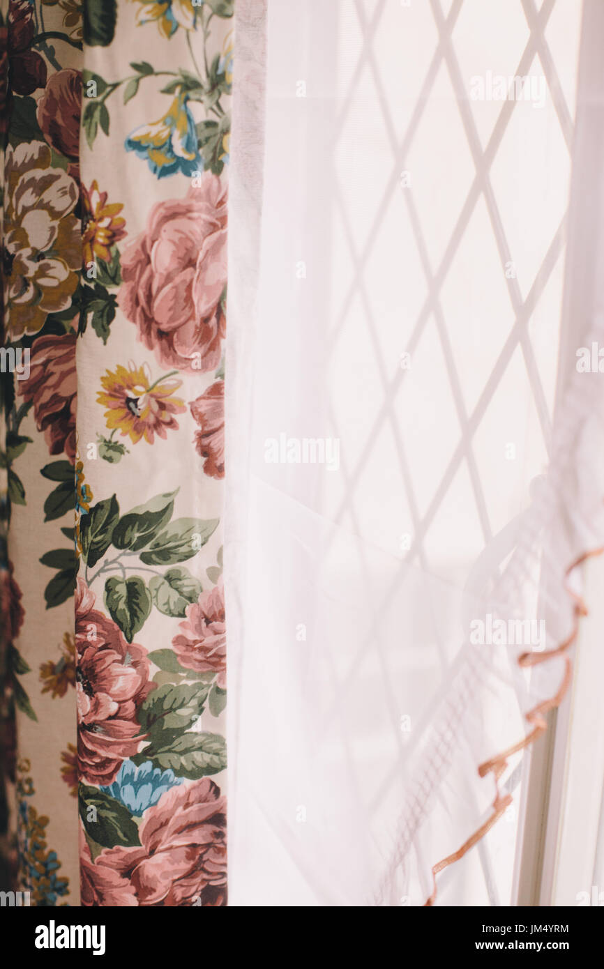 vintage curtains with flower pattern and a white net curtain in front of a leaded light