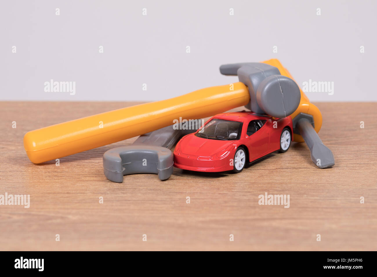 Three Plastic Toy Tools On Small Model Car Garage Repair Concept