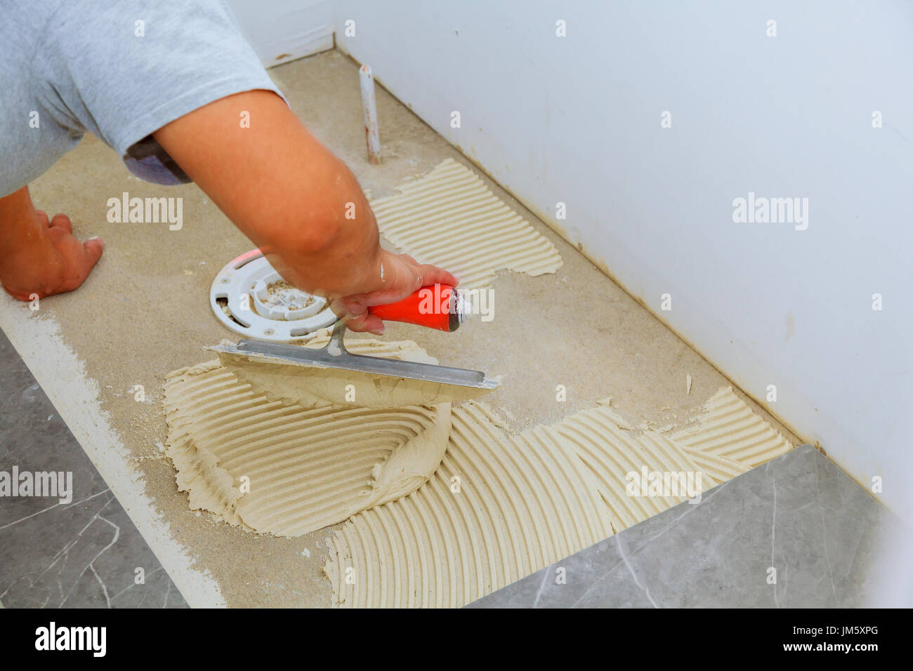 Stylish trendy white ceramic tile with a chamfer on the tiler stylish trendy white ceramic tile with a chamfer on the tiler hands in the process of laying white rectangular tiles on bathroom wall repair of apart dailygadgetfo Image collections