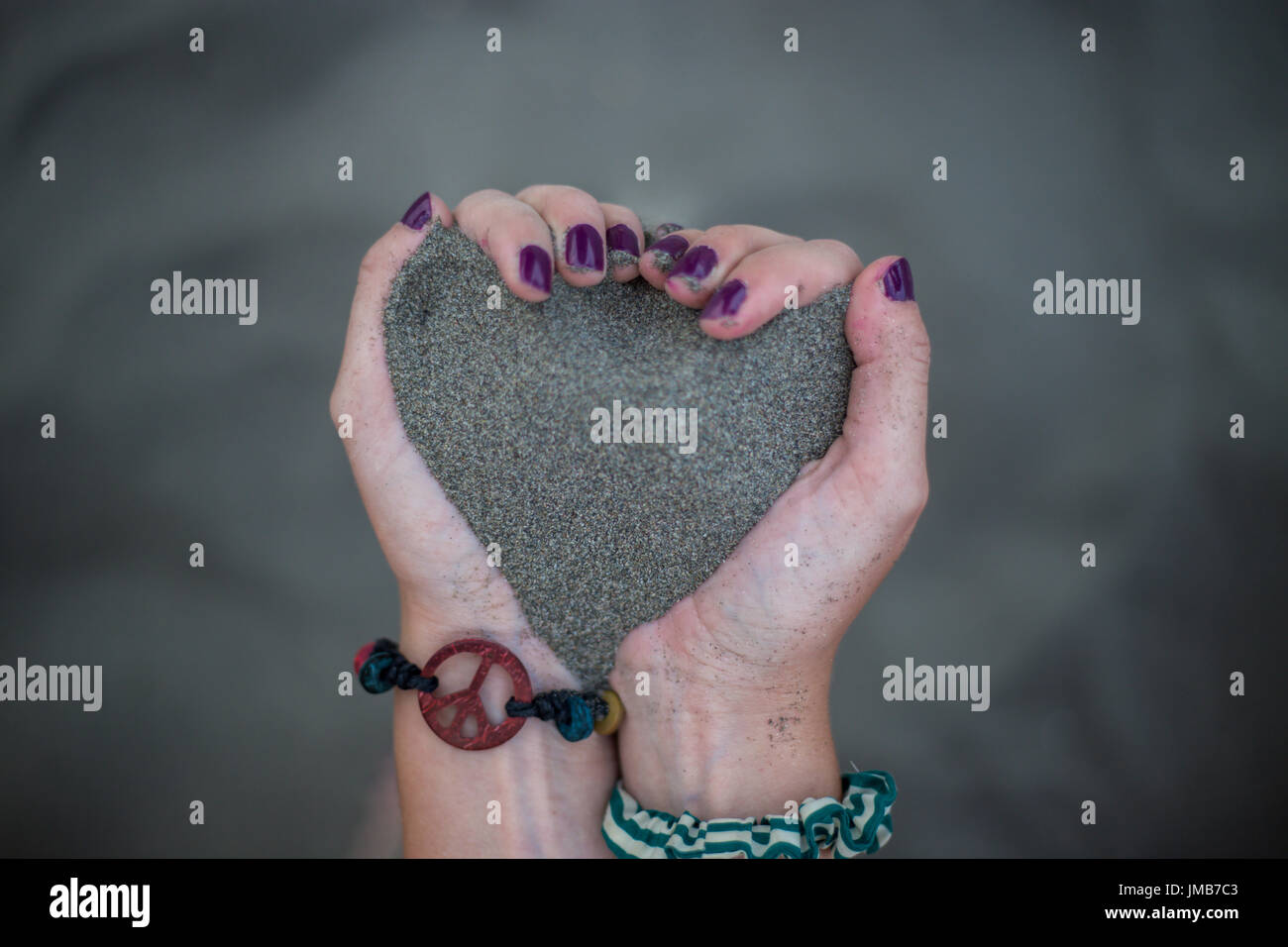 Girl keeps sand in hands in heart shape with cool and retro black ...