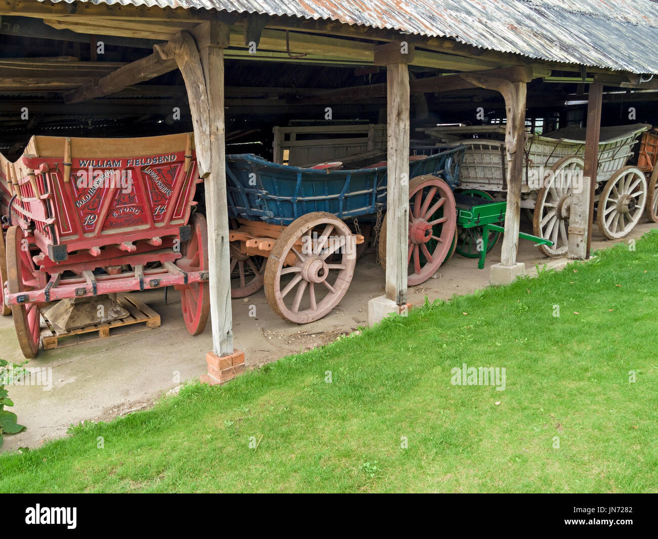 Old wooden horse-drawn farm wagon carts in old barn at ...