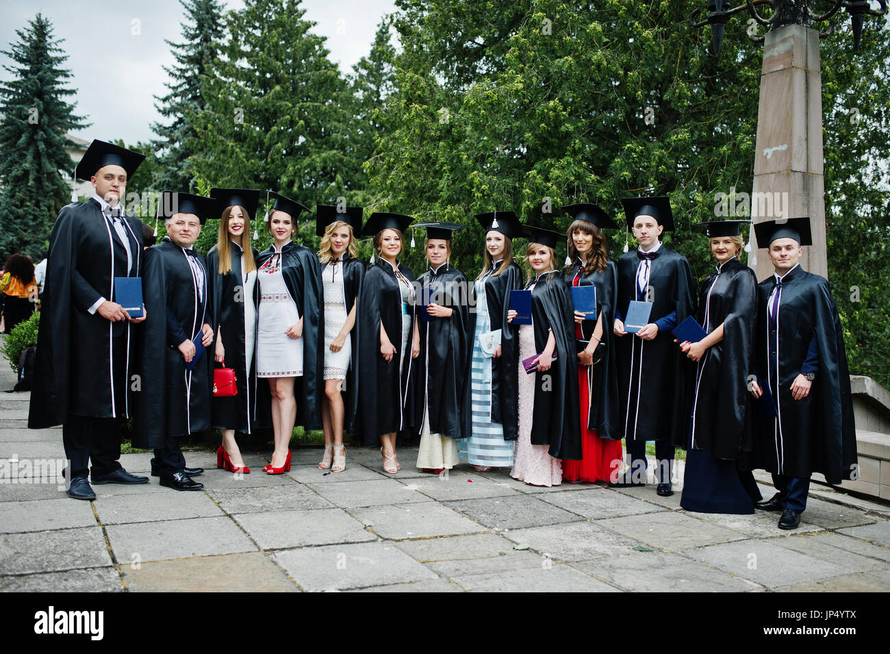 Huge group of graduates in graduation gowns and caps posing outdoor ...