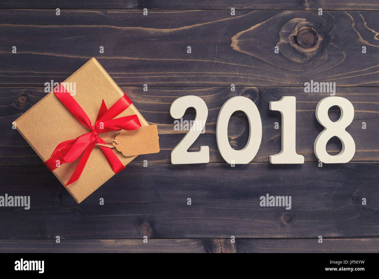 wood numbers 2018 for the new year 2018 on rustic wood background with gift box and red ribbon