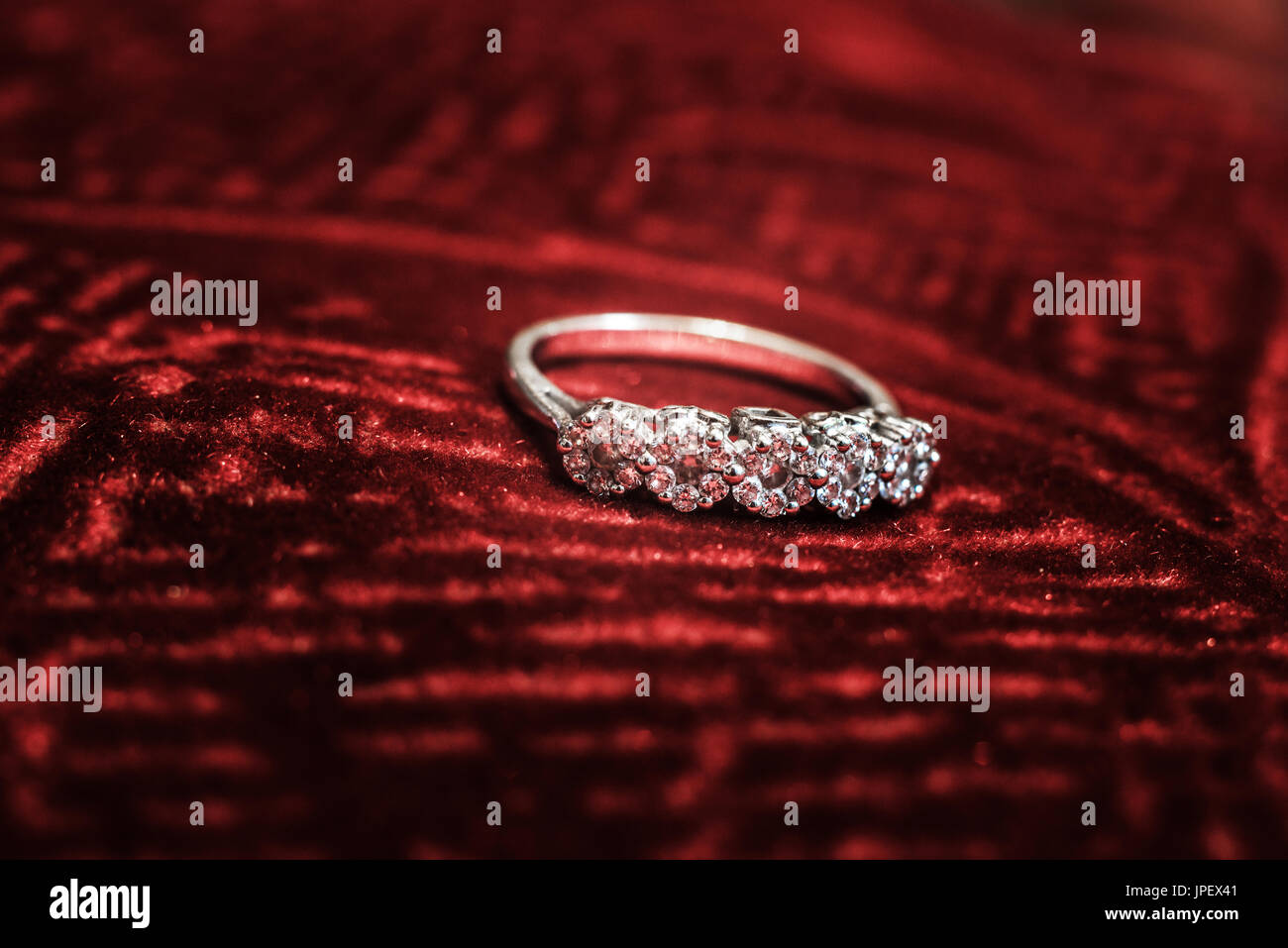 A Macro Shot Of A Diamond Ring On A Red Velvet Cloth Stock Photo