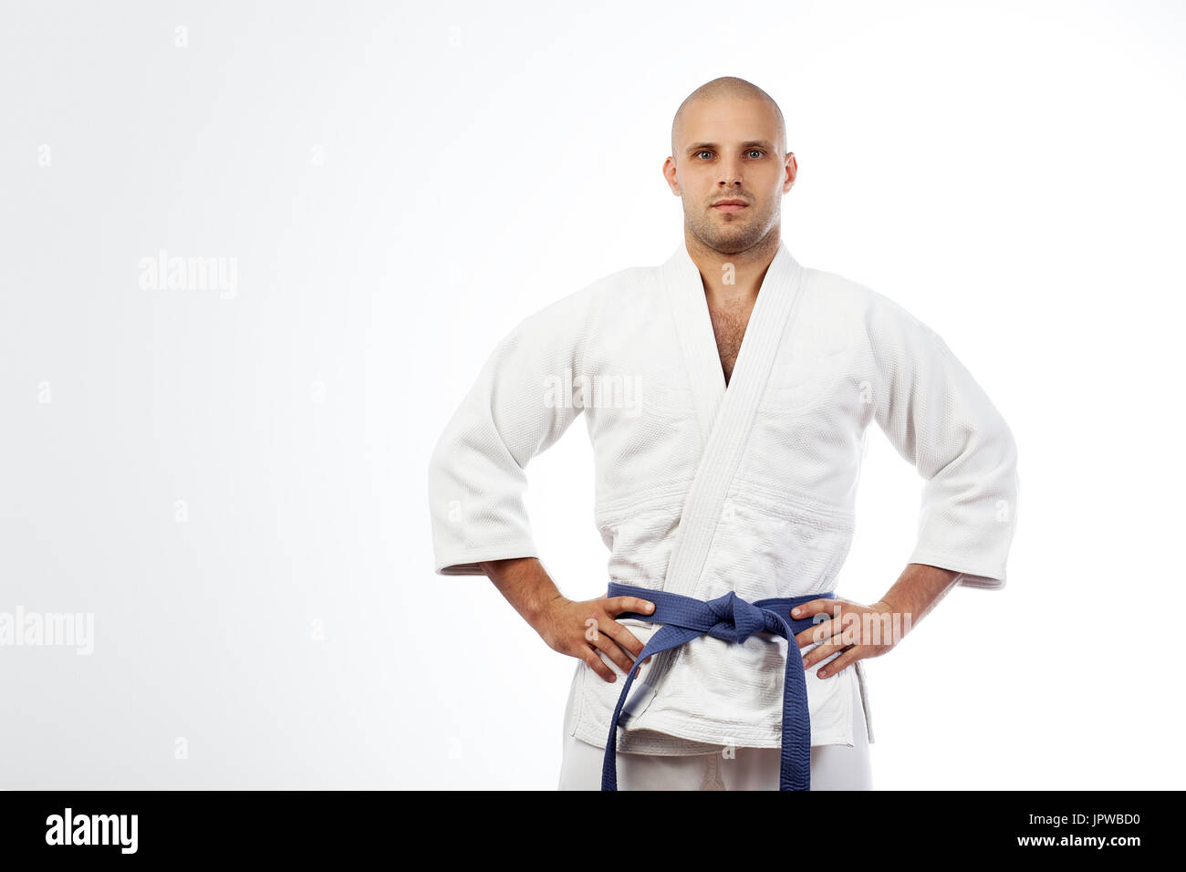 A young strong man in a white kimono for sambo, jiu jitsu and other martial