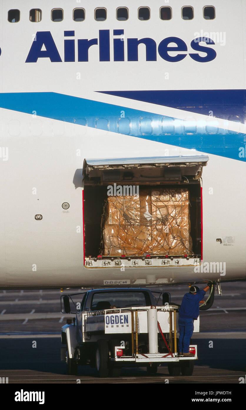 man standing on an Ogden trucvk under the open cargo door with cargo of a Nippon Cargo Airlines Boeing 747-200SF & man standing on an Ogden trucvk under the open cargo door with ...