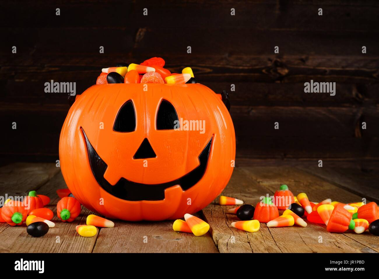 halloween jack o lantern candy holder with scattered candy on rustic