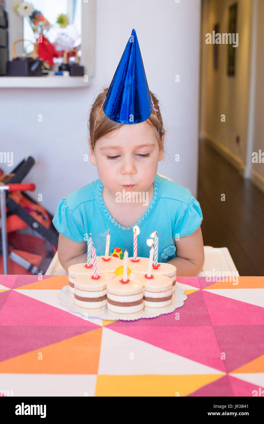 Portrait Of Three Years Old Blonde Child With Blue Cone Party Hat Blowing Lighted Candles On Birthday Cake Colorful Tablecloth At Home