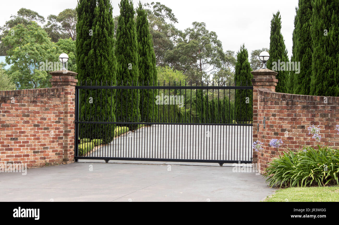 Metal driveway entrance gates set in brick fence with