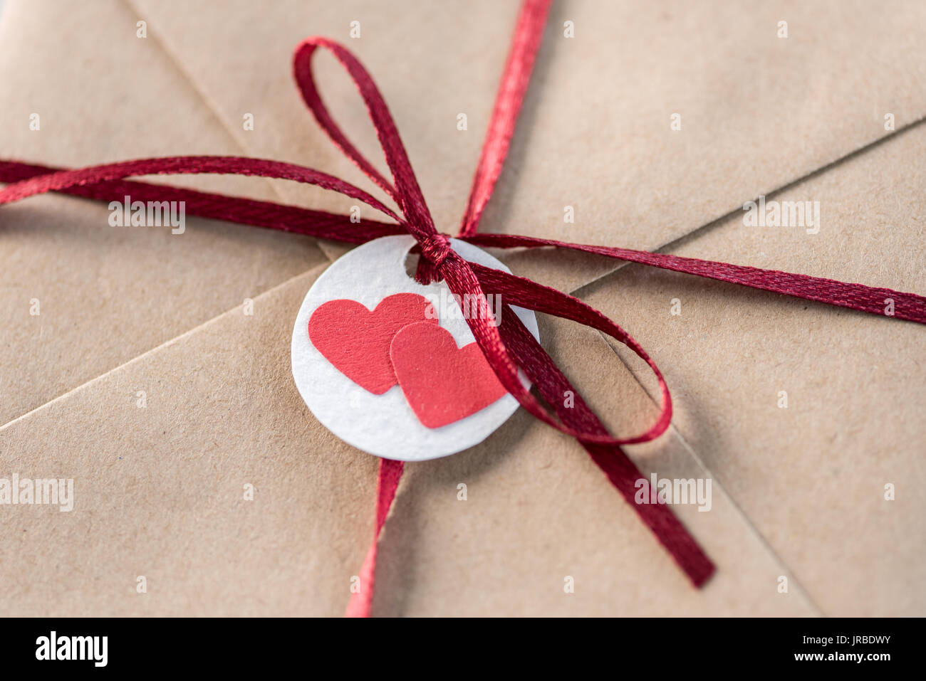 Top View Of Kraft Envelope With Tag With Two Hearts And Ribbon Stock
