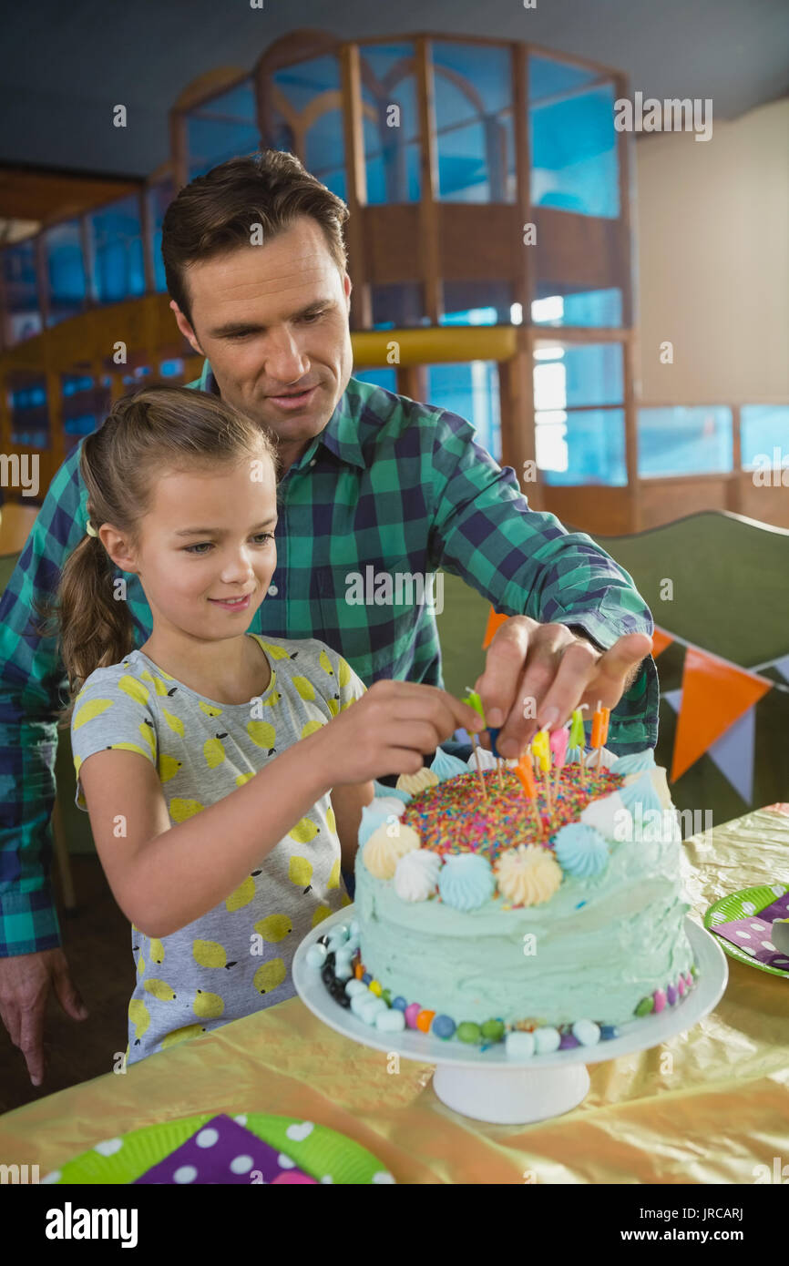 Father And Daughter Decorating Birthday Cake At Home Stock Photo