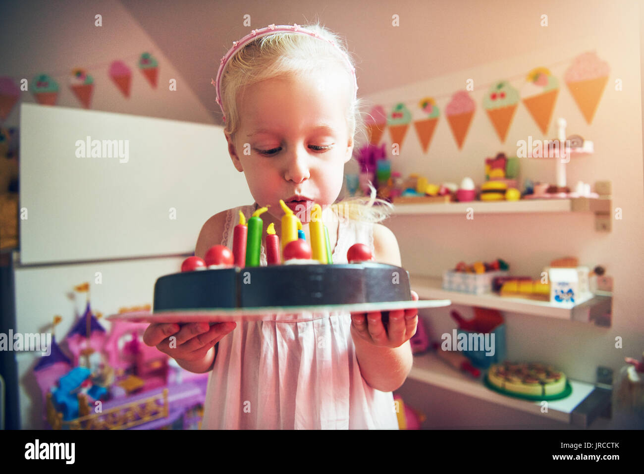 Little Girl Blowing To Candles Placed On Toy Cake Horizontal Indoors Shot