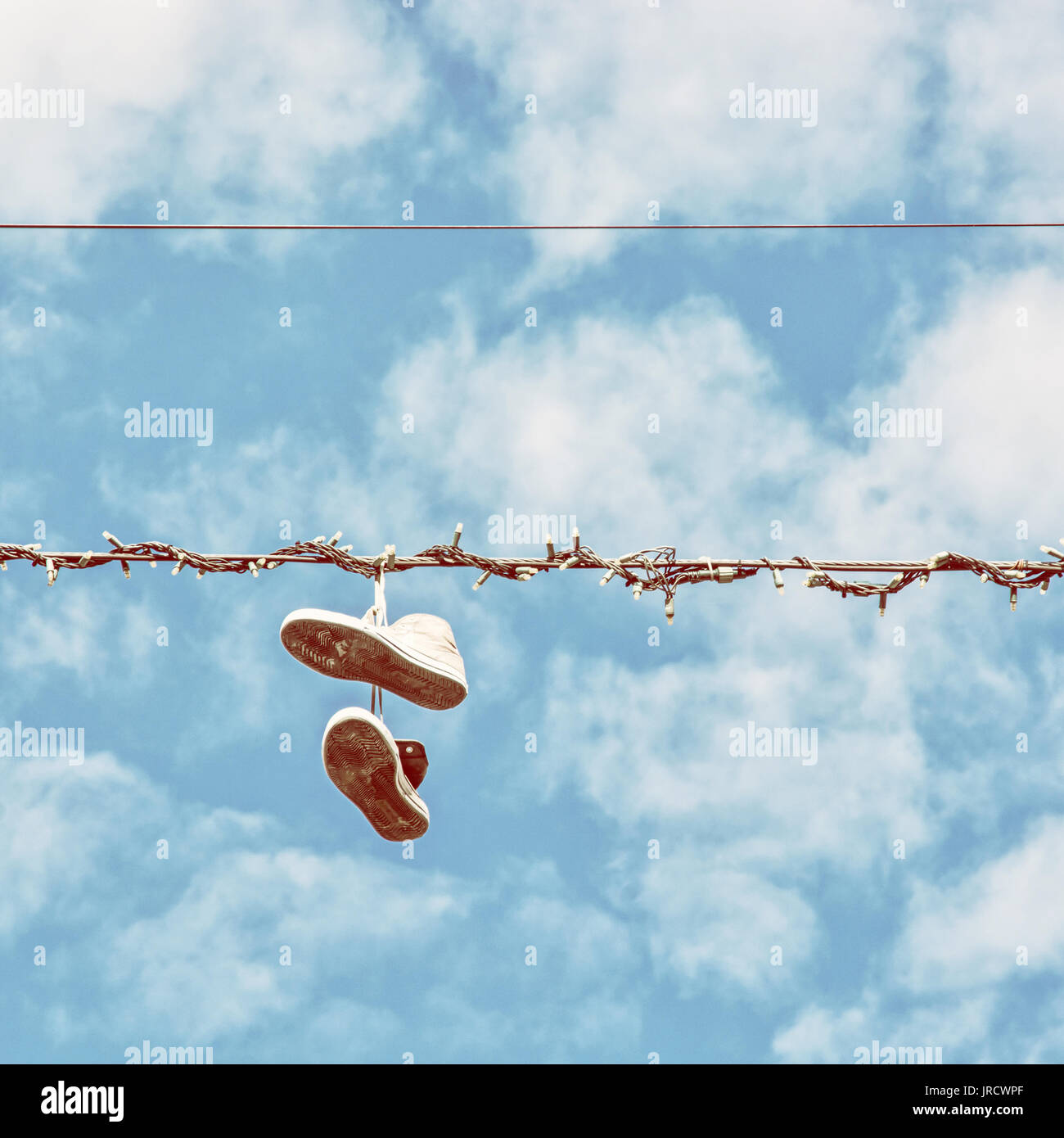 sneakers hanging on the power line blue sky bad joke retro photo