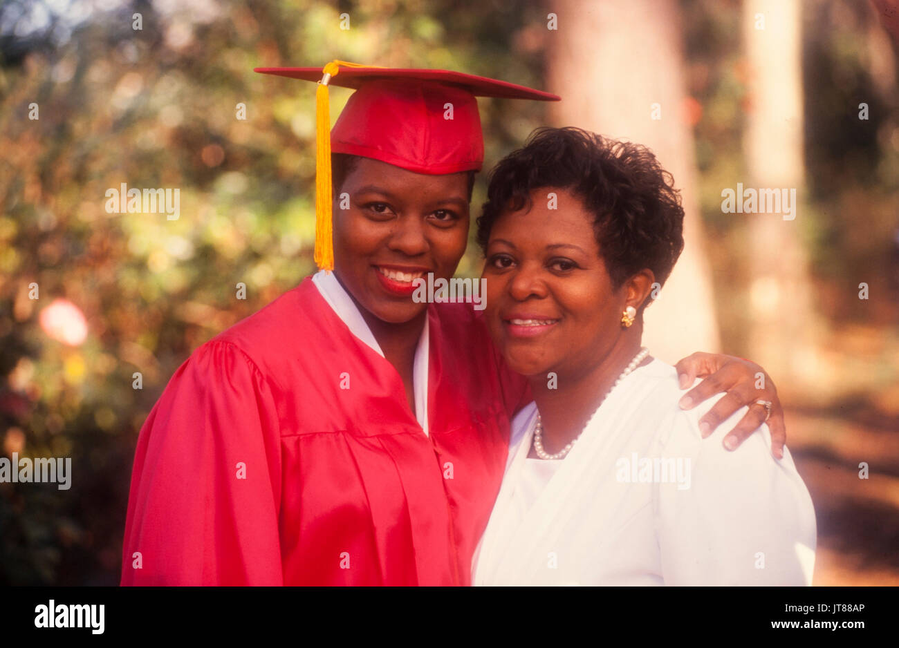 An African American graduate in her red cap and gown with a gold ...