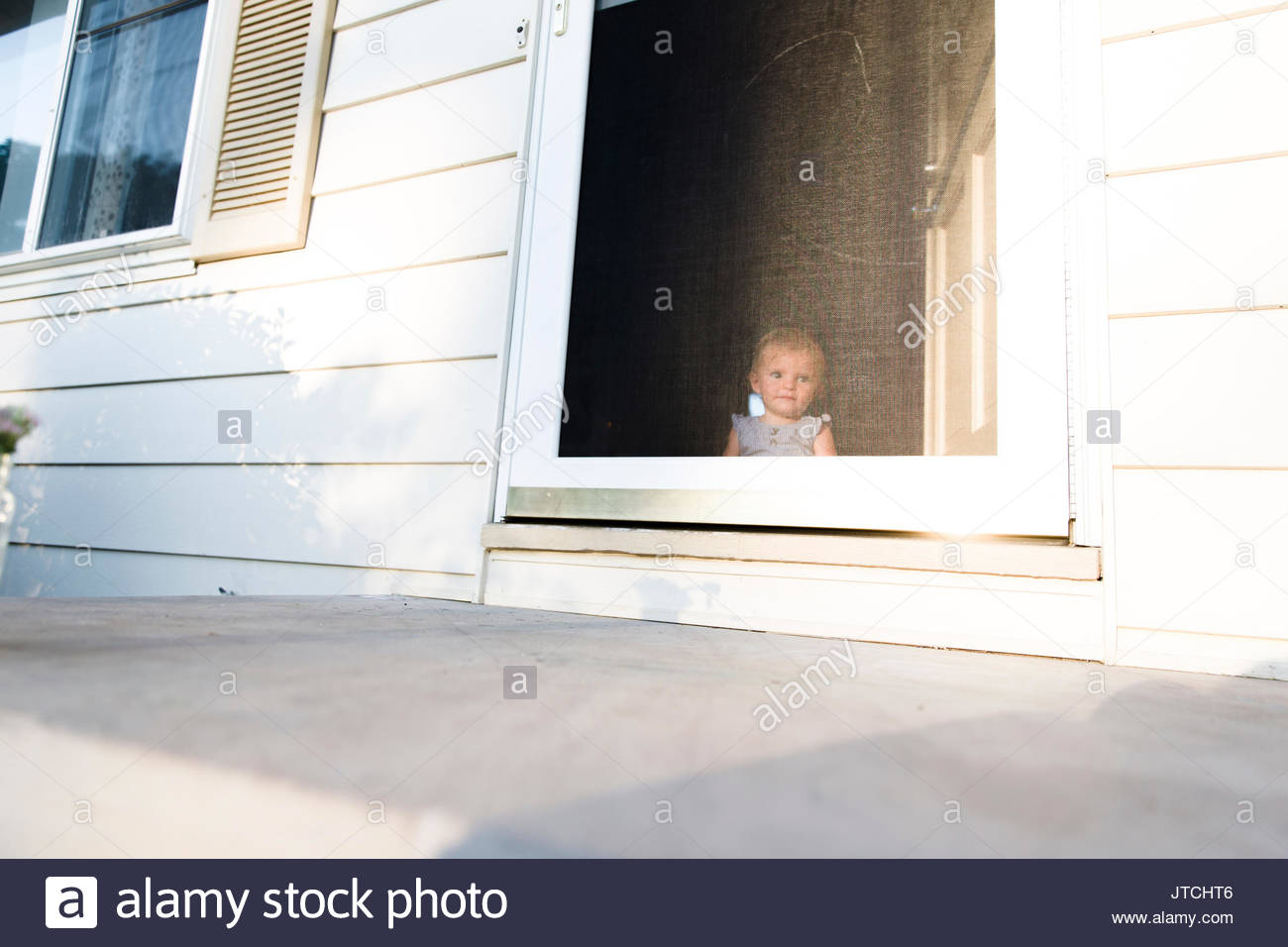 Baby Girl Sitting Looking Out Through A Screen Door Stock Photo