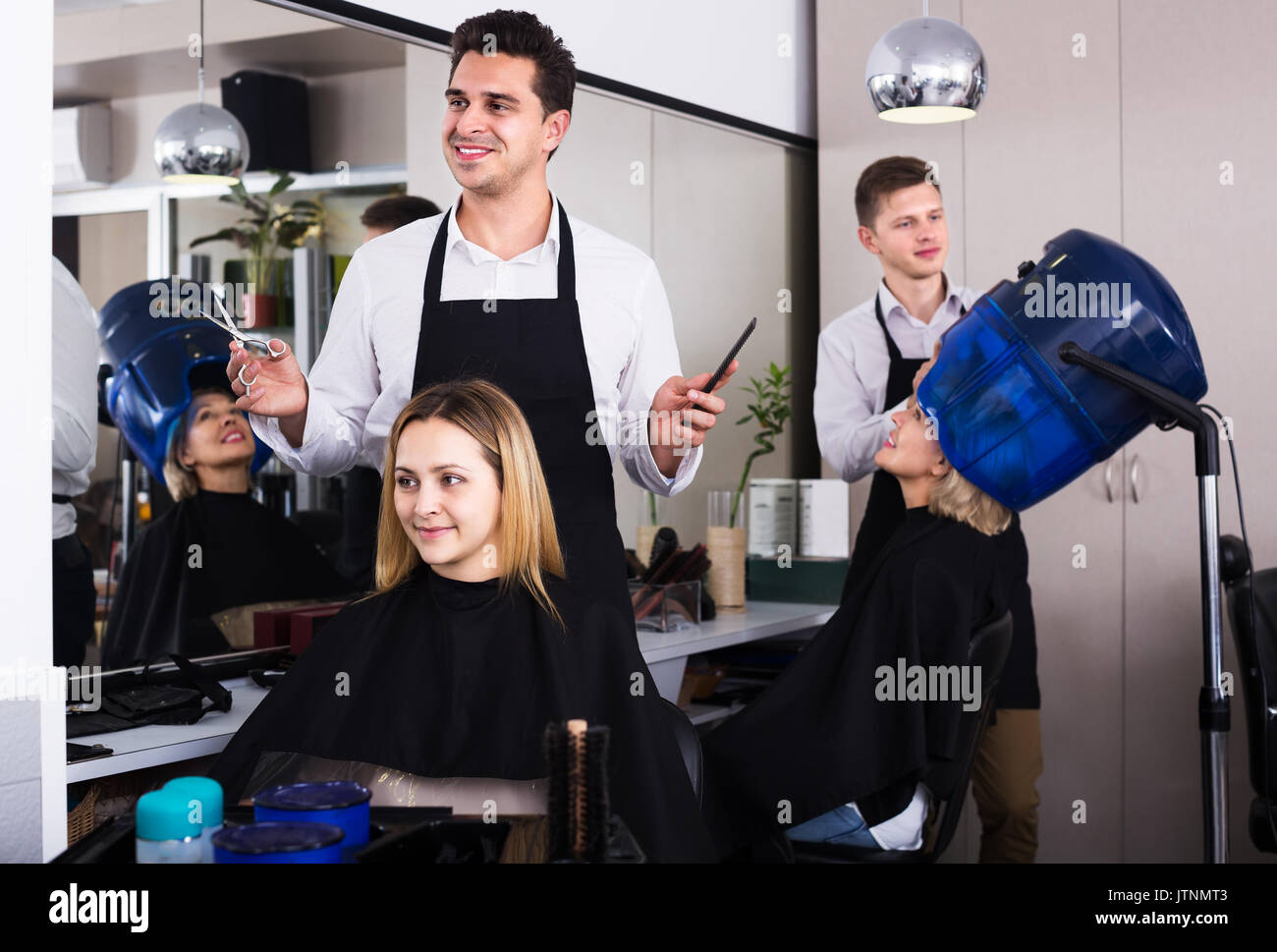 professional hairstylist cuts hair of blonde girl at the beauty salon stock image - Professional Hairstylist