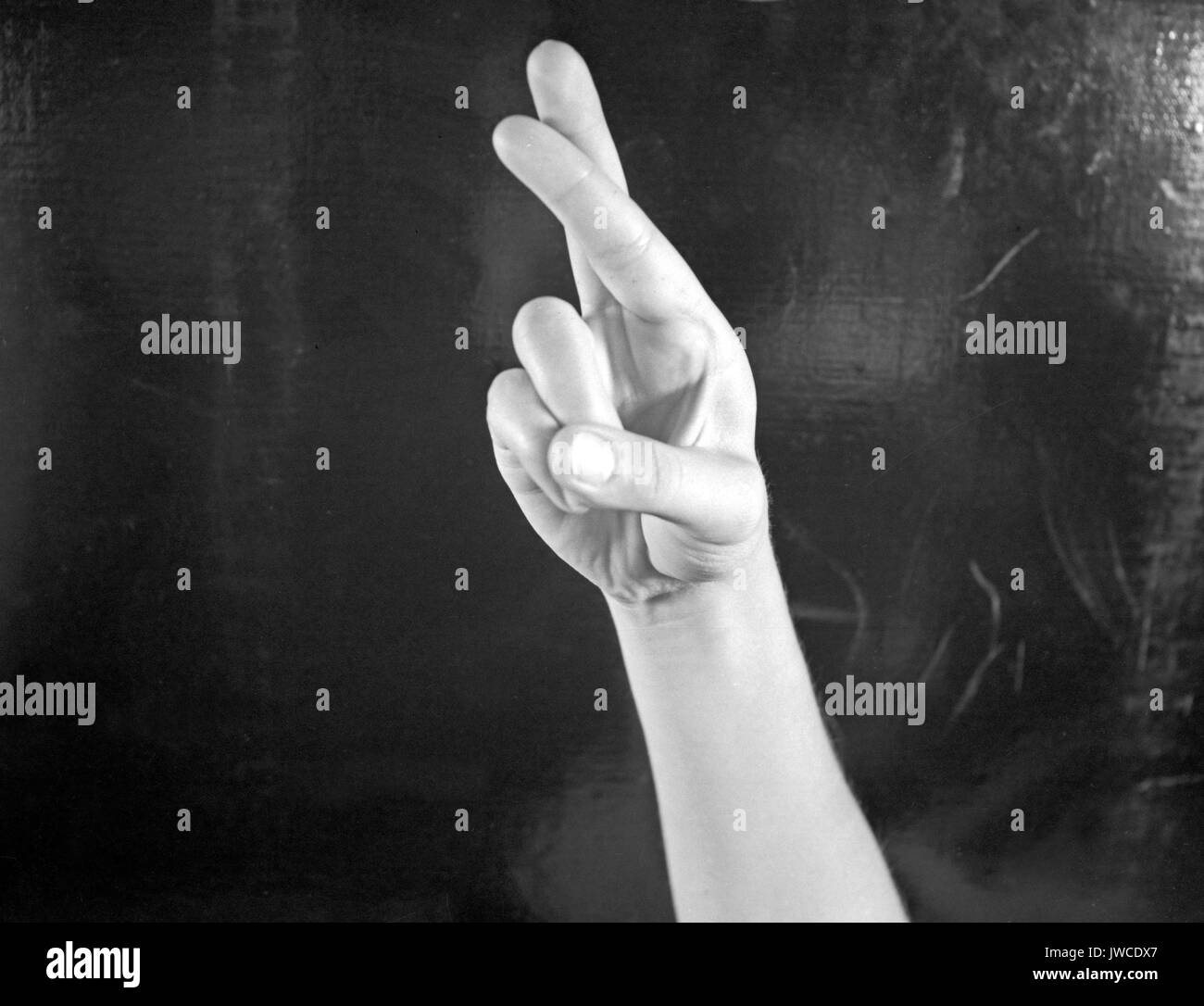 hand on black background fingerspelling the letter r in sign language