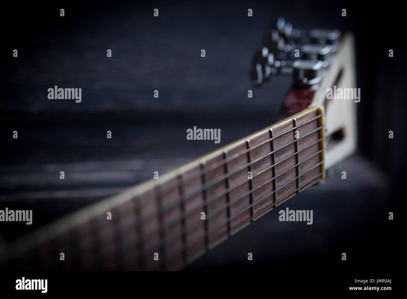 Side View Of Acoustic Guitar Neck On Black Dark Wooden Background With Selective Focus