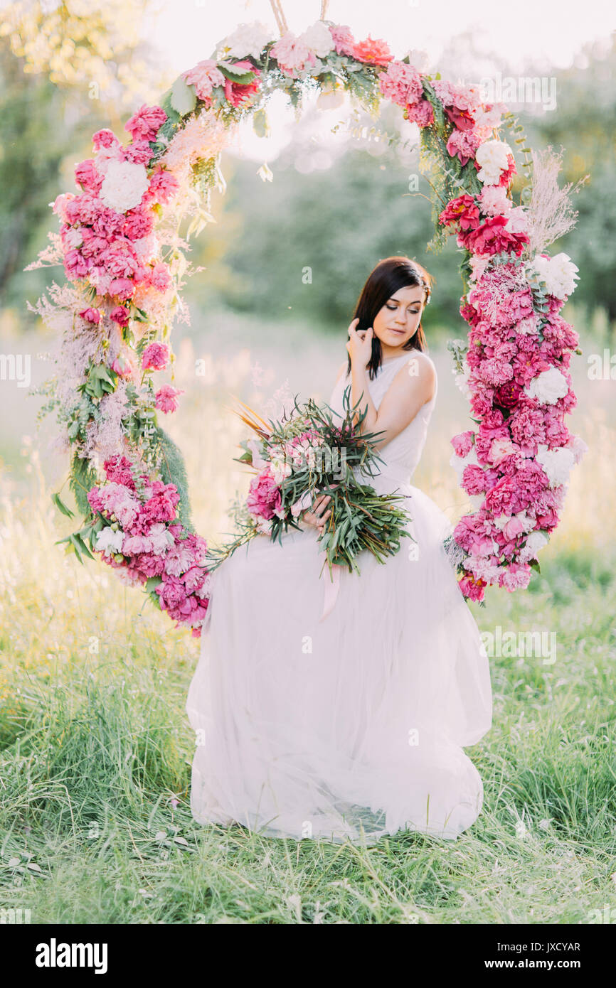 The portrait of the cute bride holding the bouquet of flowers and the portrait of the cute bride holding the bouquet of flowers and sitting in the wedding peonies arch in the sunny field izmirmasajfo