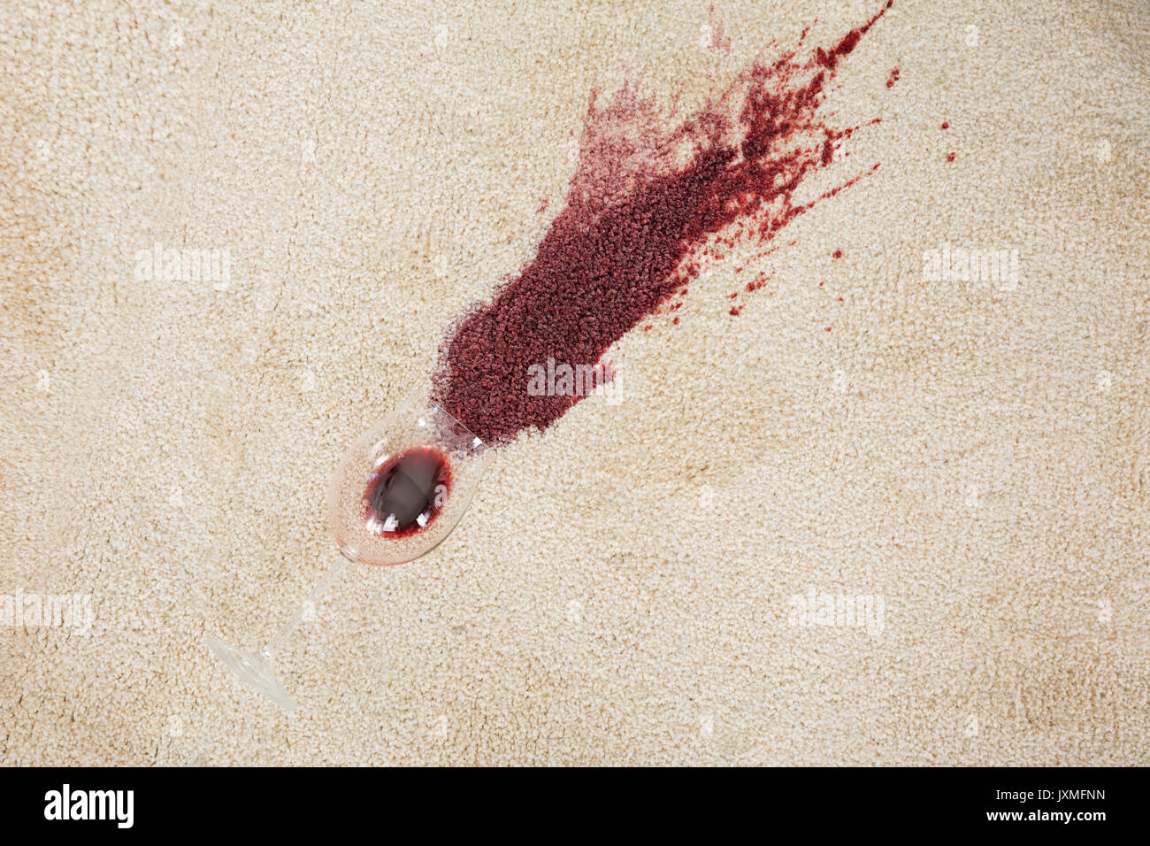 high angle view of red wine spilled from glass on carpet stock image
