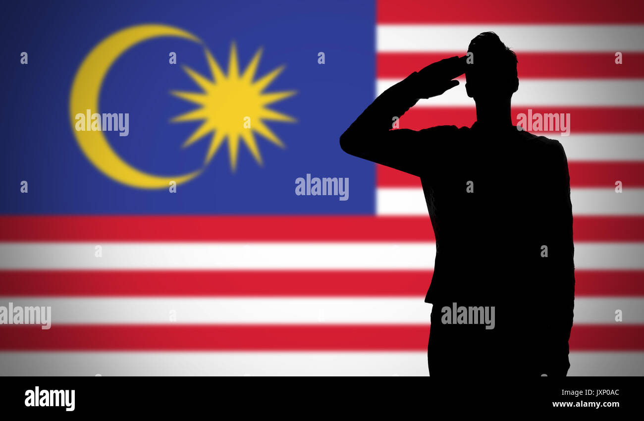 silhouette of a soldier saluting against the malaysia flag