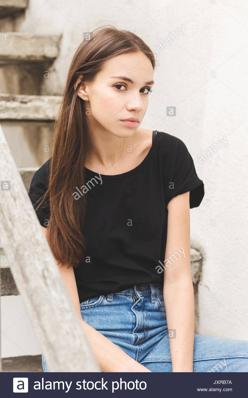 Beautiful Brunette Girl In A Black T Shirt And Mom Jeans On The Street A Woman Is Sitting On The Steps