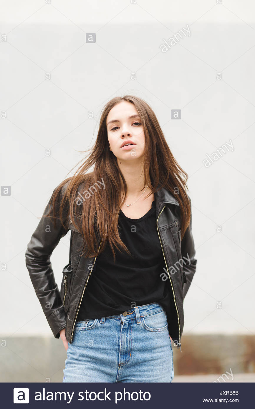 Beautiful Brunette Girl In A Black T Shirt And Mom Jeans On The Street Woman In Leather Jacket Posing Outdoors