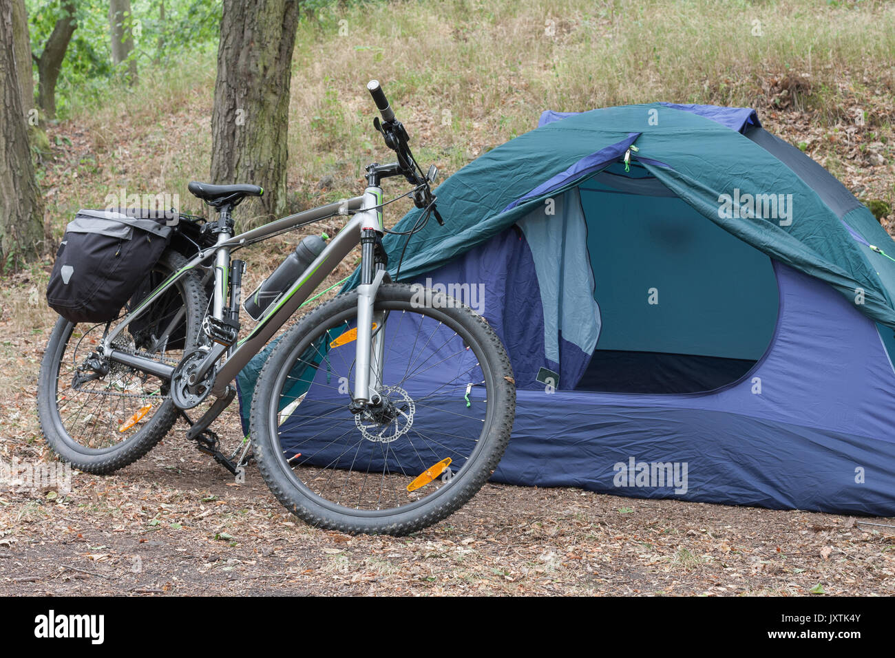 Mountain bike with saddlebags in front of tent in the woods in the summer morning . & Mountain bike with saddlebags in front of tent in the woods in the ...