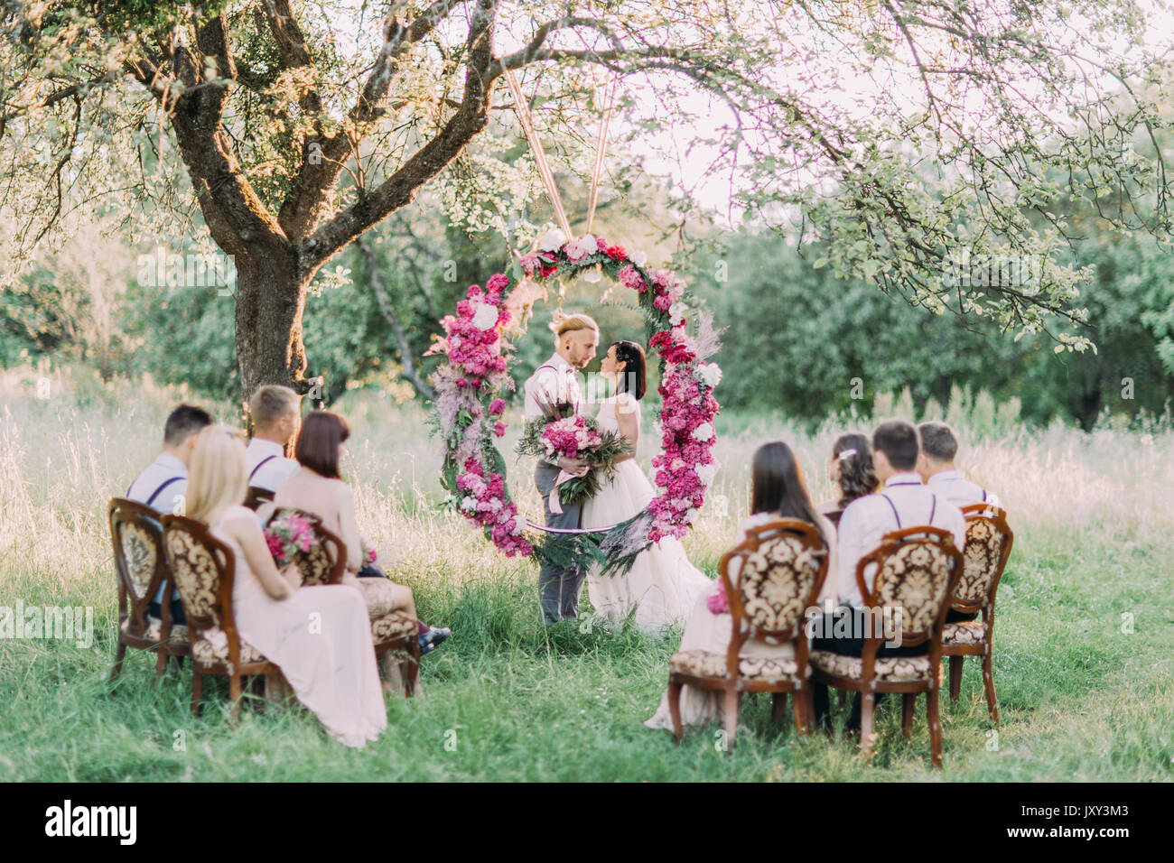 The beautiful wedding ceremony in the sunny park the horizontal the beautiful wedding ceremony in the sunny park the horizontal photo of the newlyweds with flowers behind the wedding peonies arch and their guests izmirmasajfo Gallery