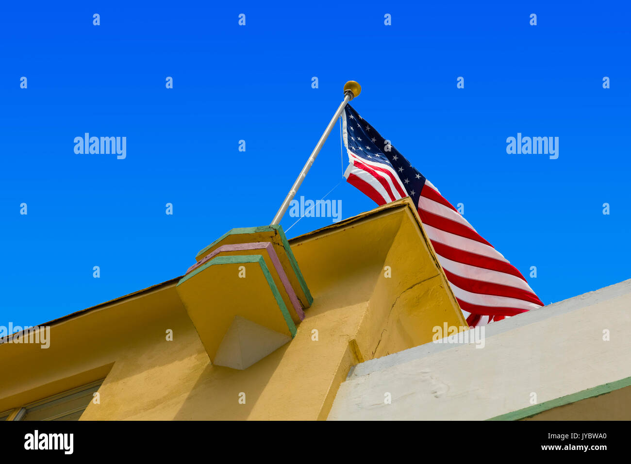 american flag on top of art deco building on ocean drive in miami