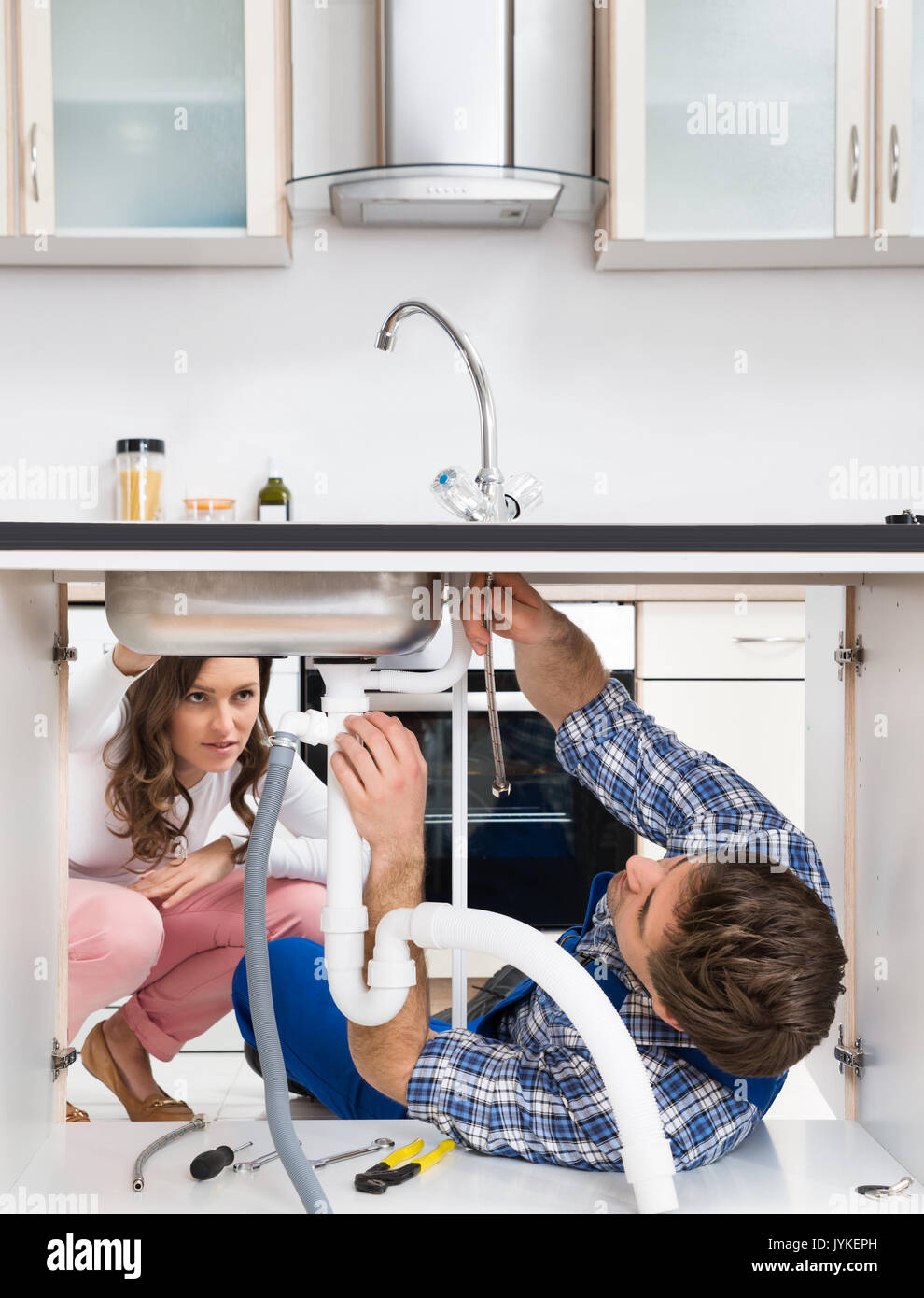 Young Worker Fixing Sink In Front Of Woman Crouching On Floor In ...