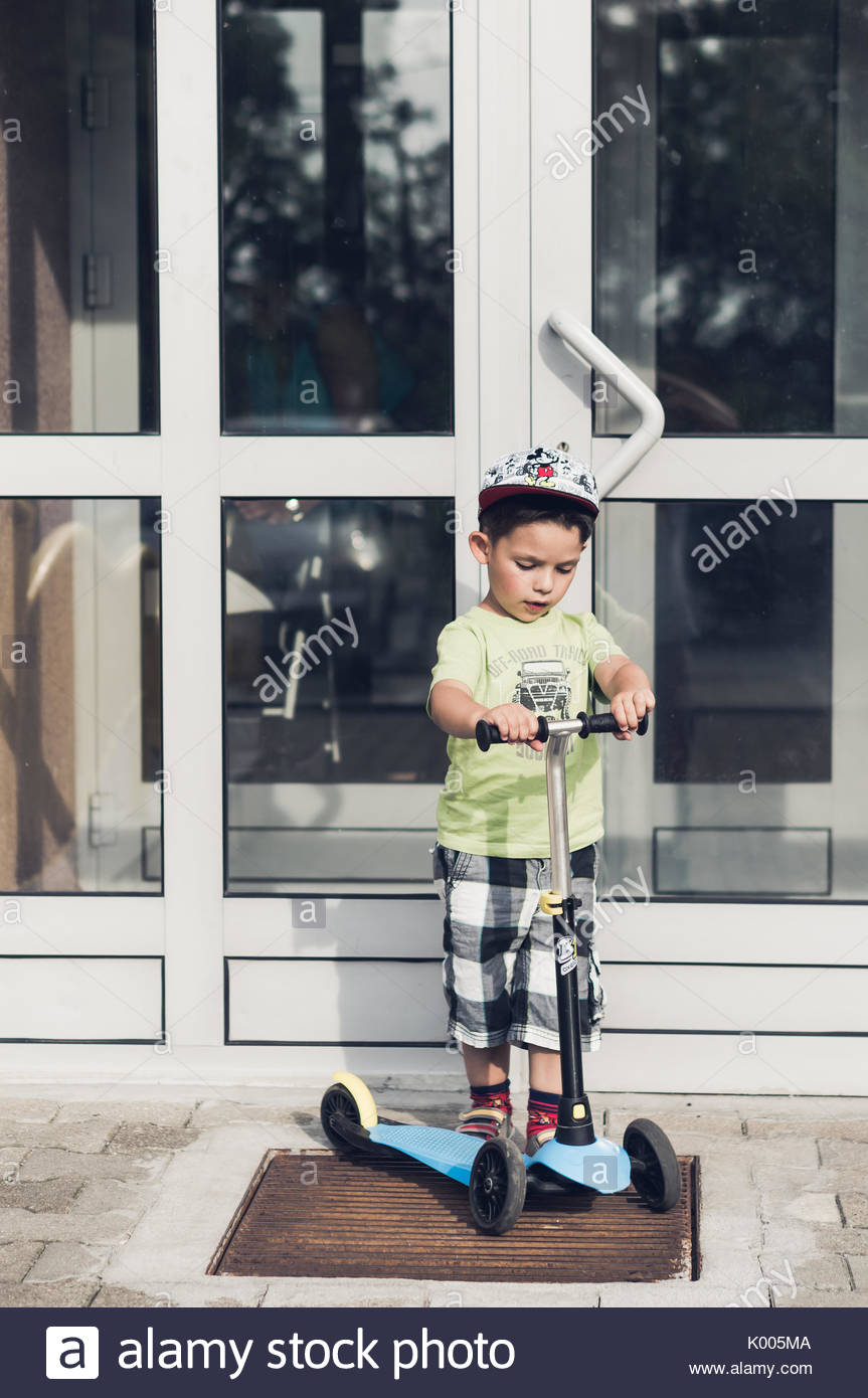 Toddler Boy Standing On A Small Child Scooter In Front Of A Closed