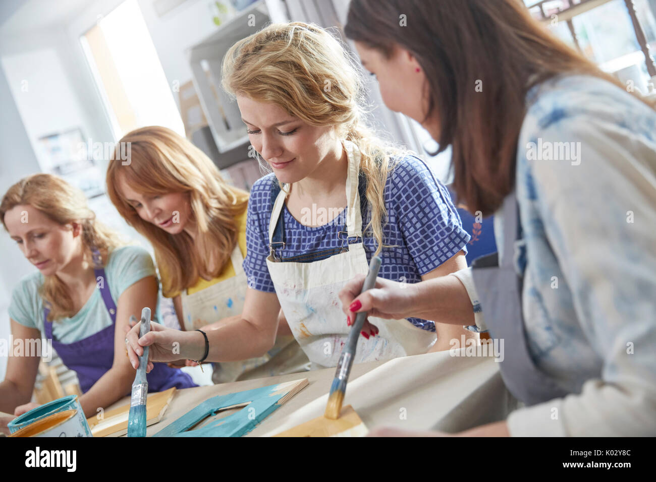Female artists painting picture frames in art class workshop Stock ...