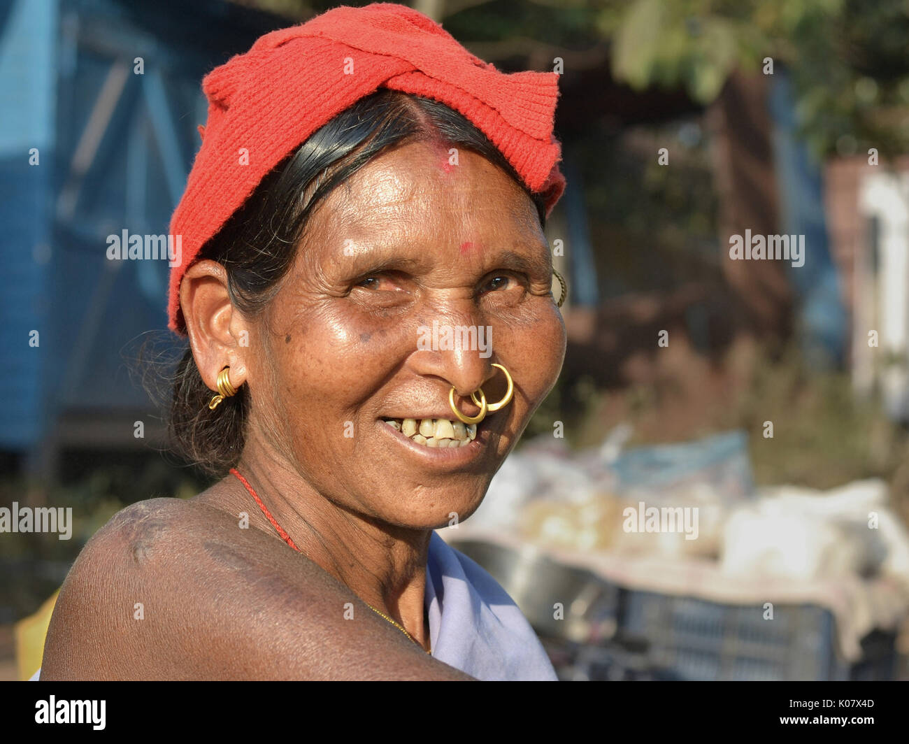 Elderly Indian Adivasi market woman with two golden nose rings and ...