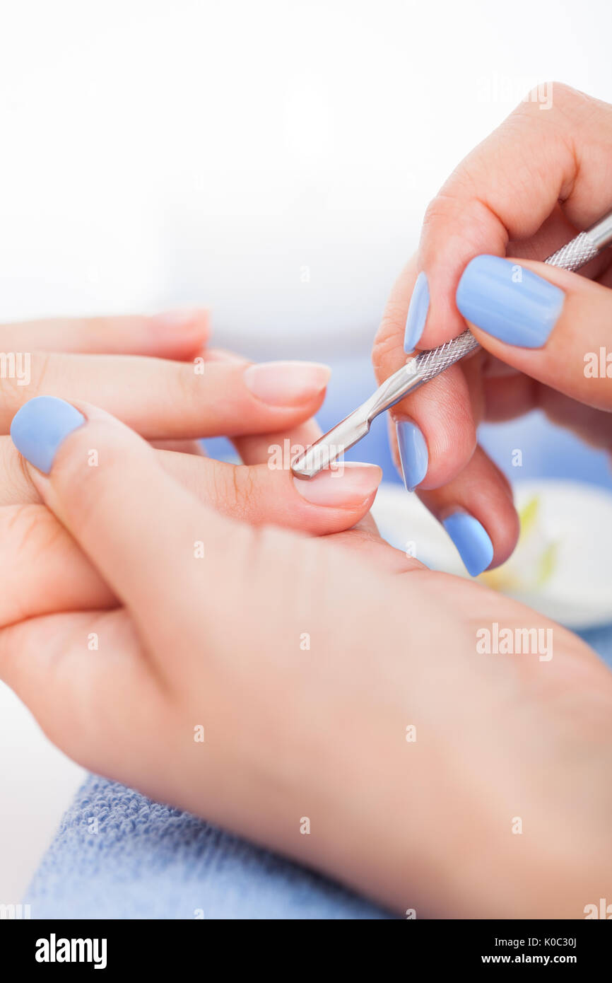 Cropped image of manicurist removing cuticle from the nail of woman ...