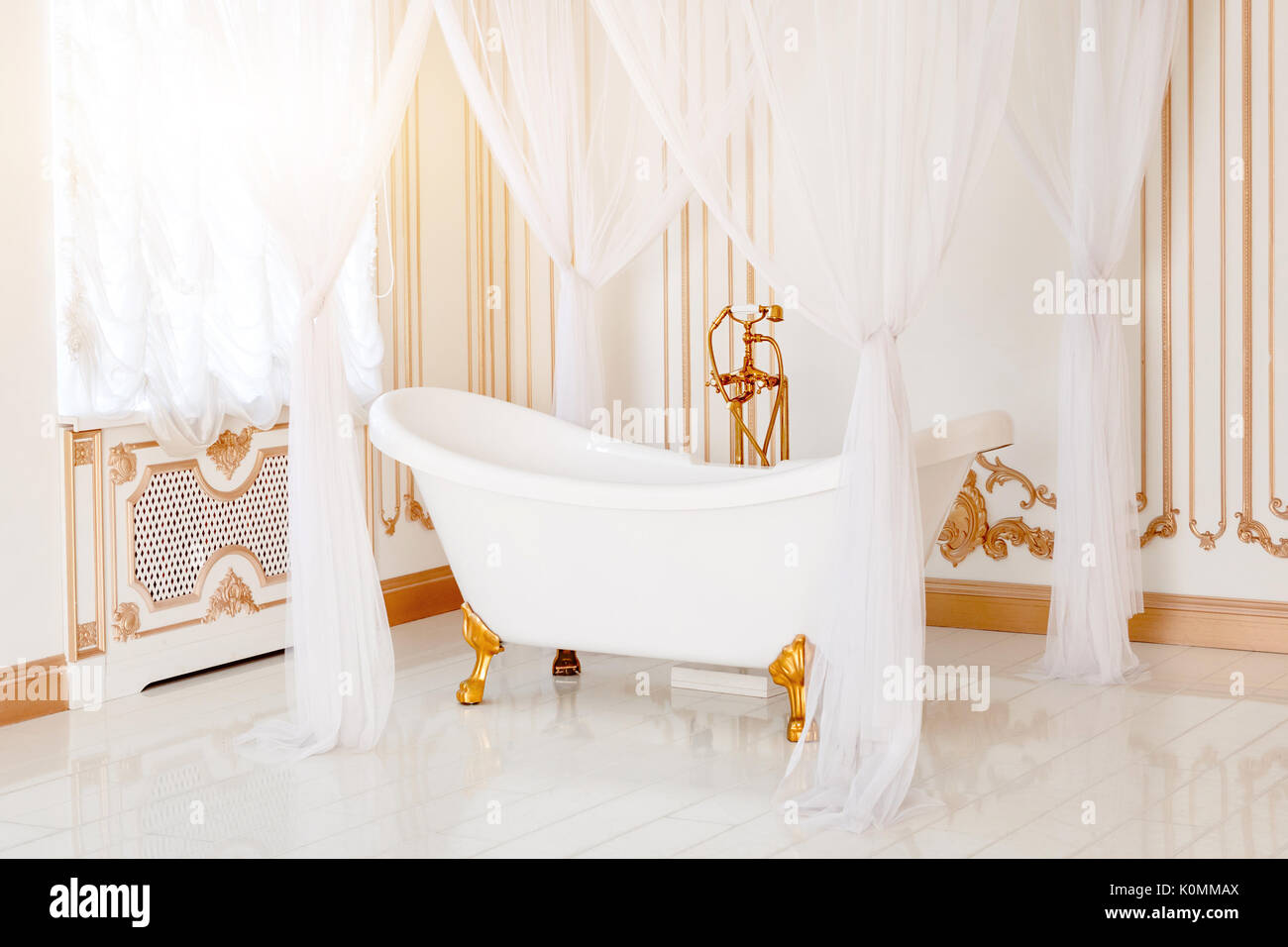 Luxury bathroom in light colors with golden furniture details and ...
