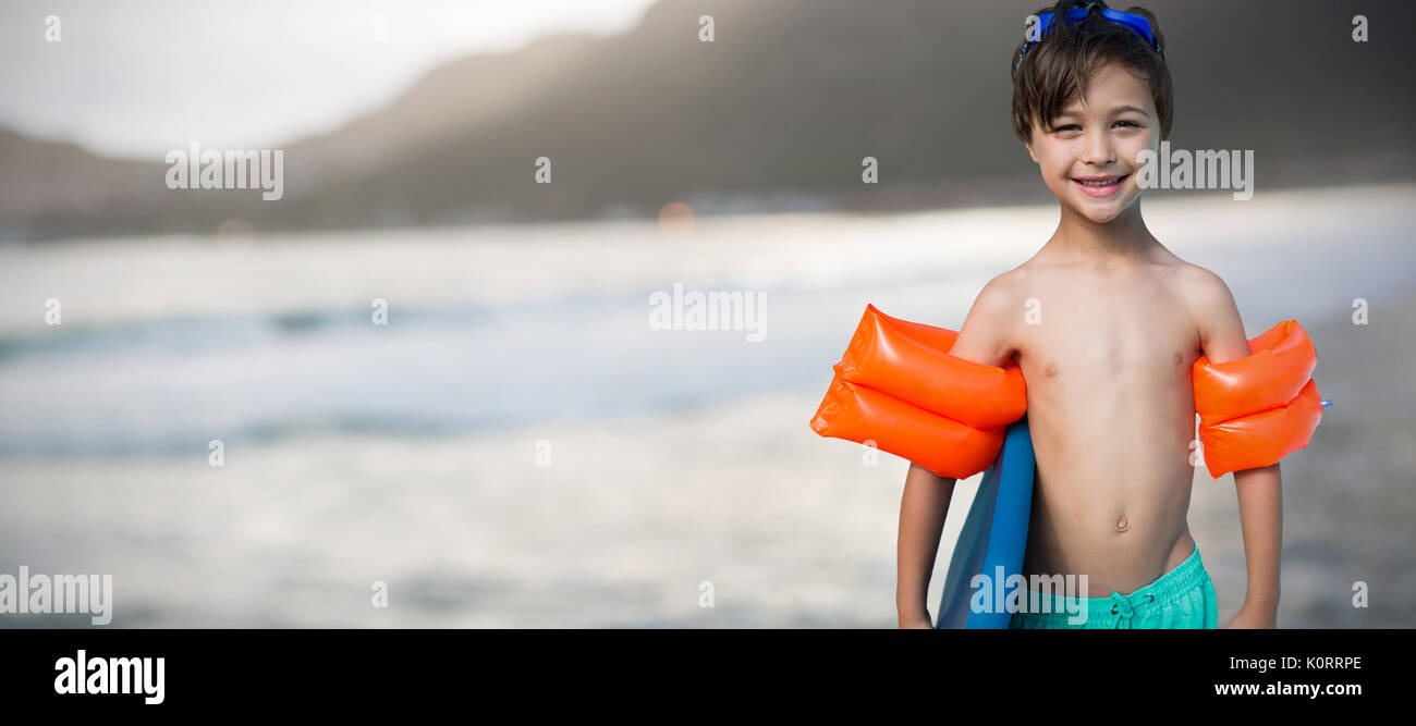 26c45e7abd Portrait of shirtless boy carrying swimming float against mountain against  sky at beach
