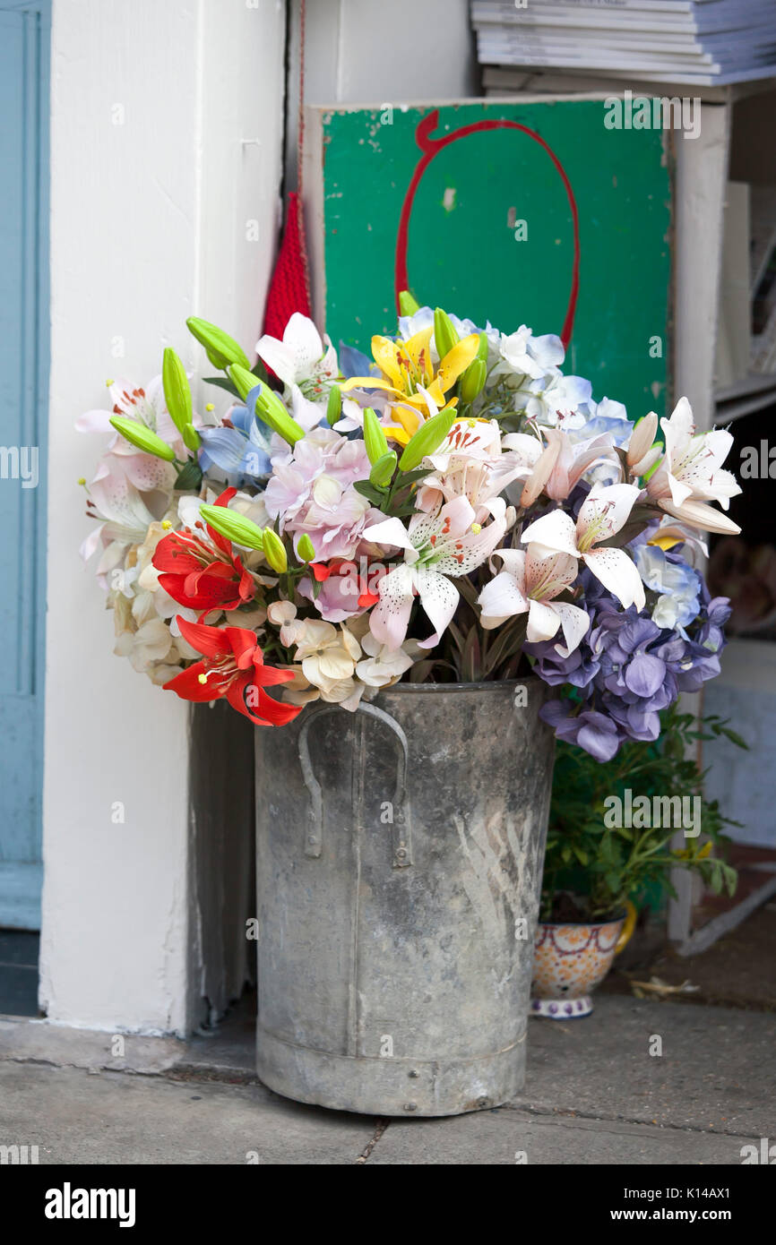 A bouquet of artificial flowers yellow red orange lilies and a bouquet of artificial flowers yellow red orange lilies and blue hydrangeas in a zinc high bucket near the entrance to the house mightylinksfo