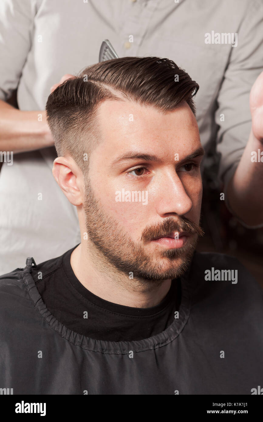 The Hands Of Barber Making Haircut To Young Man In Barbershop Stock