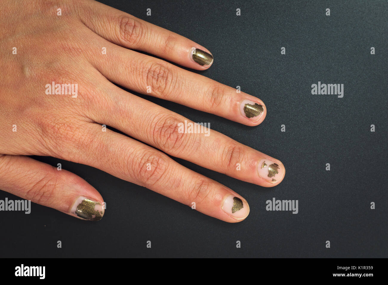 Glitter dark color Nails polish scratched on black background with ...