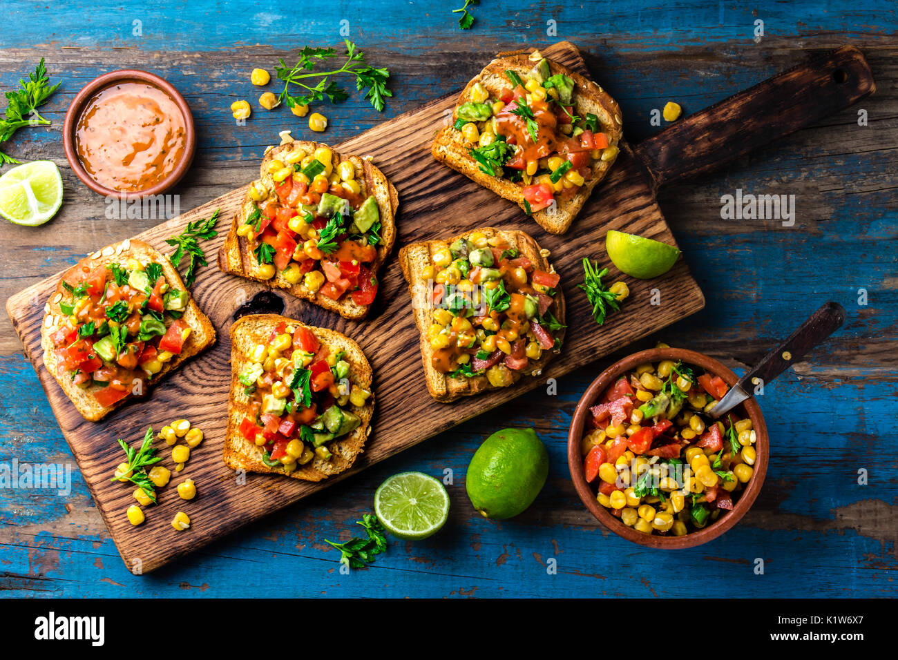 Mexican latin american style open sandwiches vegetarian toasts with mexican latin american style open sandwiches vegetarian toasts with maize avocado tomatoes on wooden board rustic wooden blue background top view forumfinder Image collections