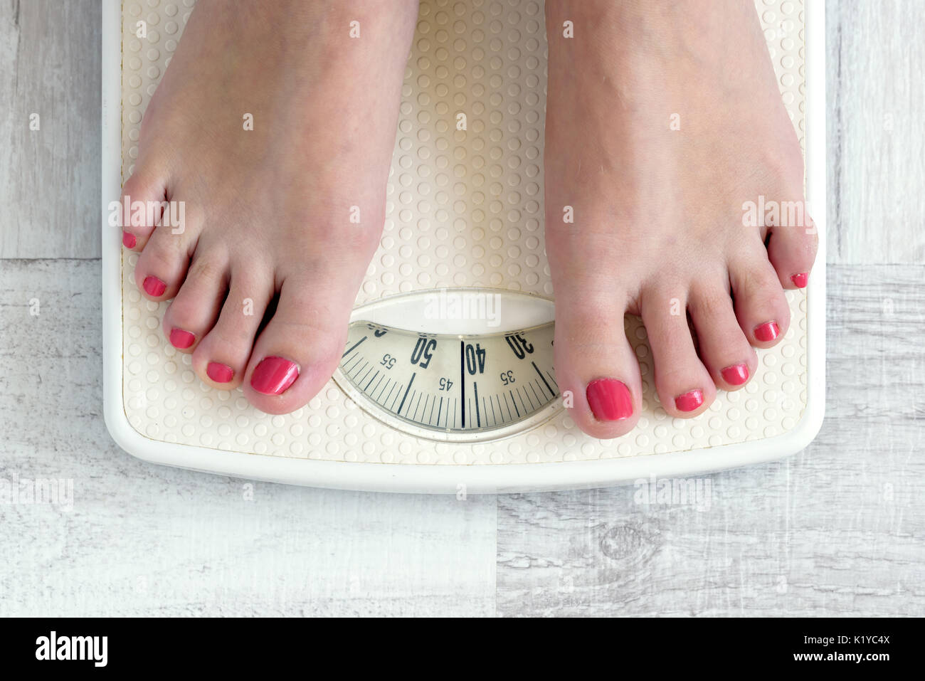 Female Feet Standing On A Bathroom Scale Concept Of Diet