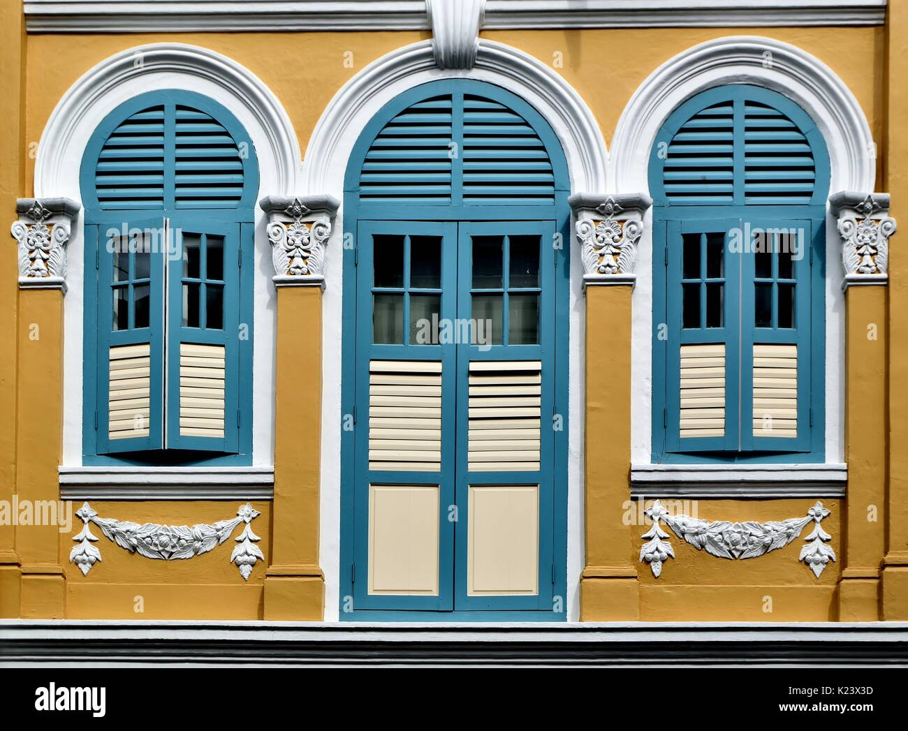 Traditional shop house exterior with blue wooden louvered shutters ...