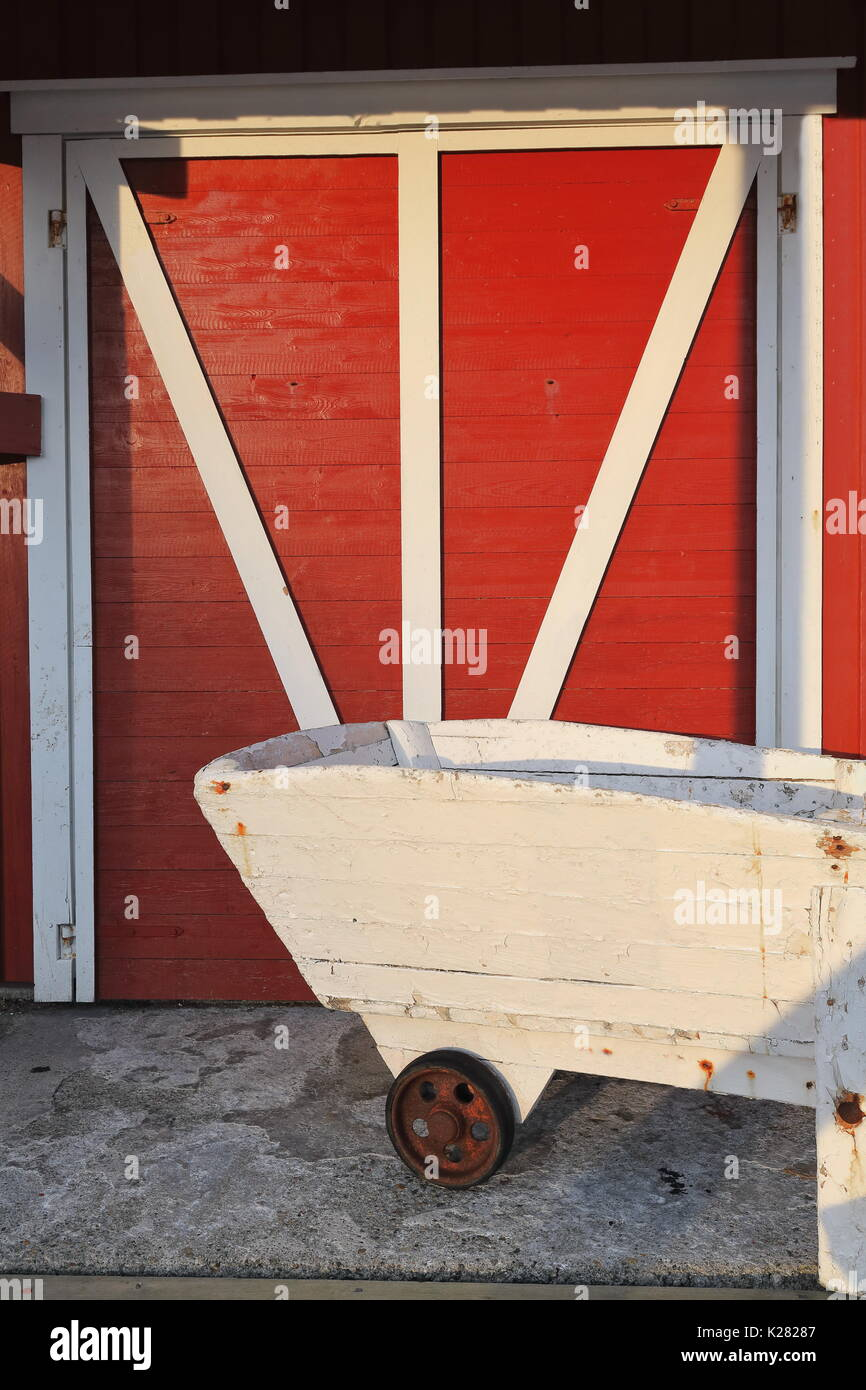 Battened and braced closed door of rorbu-traditional seasonal fishing hut-red cottage-white wooden wheelbarrow in front at the entrance porch. A i Lof & Battened and braced closed door of rorbu-traditional seasonal ...