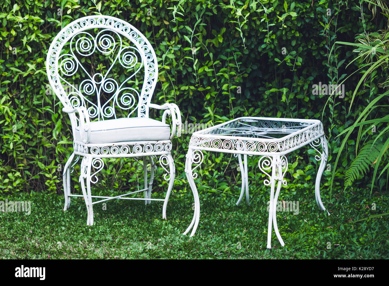 Old vintage furniture in garden with natural green background. White metal  chair and table, - Vintage Garden Furniture Stock Photos & Vintage Garden Furniture
