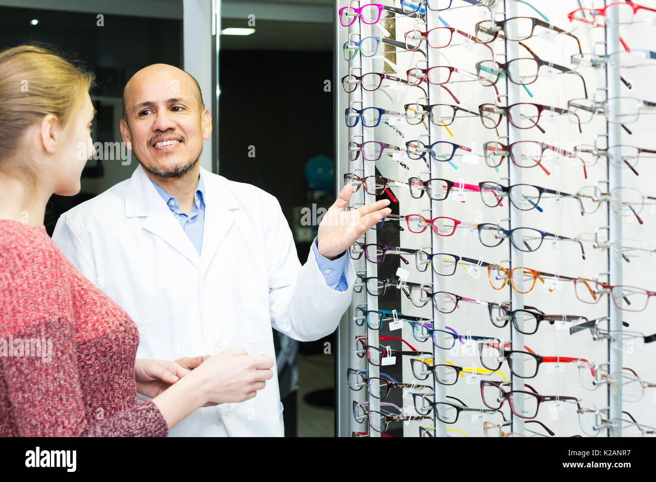Senior smiling male optician offering glasses frames to positive ...